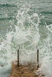 Wave con schiuma che si rompe contro la riva Fotografia Stock