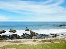 Wave contro le rocce sulla spiaggia Fotografia Stock