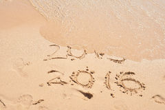 The wave is covering the digits 2015. New Year concept. Inscription 2015 and 2016 on a beach sand. Happy New Year 2016. Stock Images