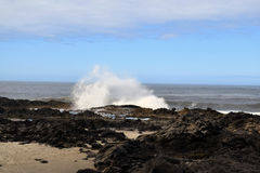 Oregon Coast Waves Splash. Wave crashes against dark rocky coast with blue sky over ocean on Oregon coast Stock Image