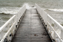 Wave crashes along a jetty. Rough waves ripple through a jetty on a wet and rainy day Royalty Free Stock Images