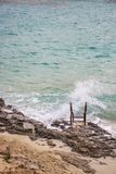Wave crashes over a beach ladder on the shore of Blue Lagoon Bay, Comino coastline, Comino island, Malta. Wave crashes over the beach ladder on the shore at Blue Royalty Free Stock Photos