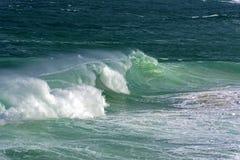 Wave crashing against rocks on the beach Royalty Free Stock Photo