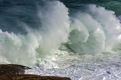 Wave crashing against rocks on the beach Stock Images