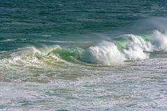 Wave crashing against rocks on the beach Royalty Free Stock Image