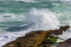 Wave crashing against rocks Stock Photos