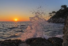 The wave crashing against the stone and reflected in the rays of. The wave with splash crashing against the stone and reflected in the rays of the setting sun royalty free stock images