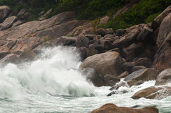 Wave crashing against stones at the rocky beach - power of natur Royalty Free Stock Photography