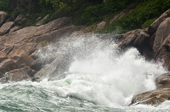Wave crashing against stones at the rocky beach - power of natur Royalty Free Stock Images