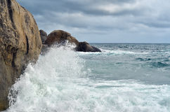 Wave crashing against stones at the rocky beach - power of natur Royalty Free Stock Photos