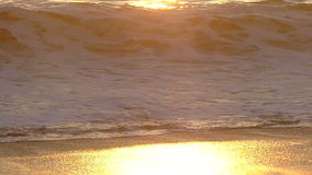 A Wave Crashing on The Beach at Sunset in Slow Motion stock video