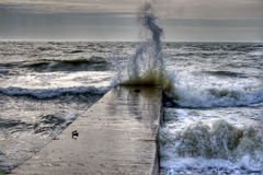 Wave crashing on breakwater. View of a wave crashing into a concrete breakwater or jetty with spray shooting into the air Royalty Free Stock Photography