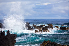 Wave Crashing Onto Volcanic Rock, Maui, Hawaii. Blue waves of the Pacific Ocean crashing onto the volcanic rock of the eastern shore of the island of Maui Royalty Free Stock Photography