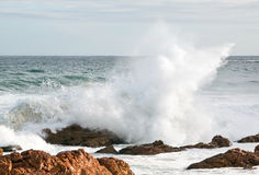 Wave crashing over brown rocks Stock Photo
