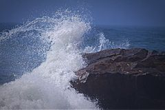 Wave Crashing over Rock. Wave hitting boulder on rocky beach Royalty Free Stock Images