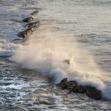 Wave crashing over rocks in ocean at sunrise with long exposure. Wave crashing over rocks in ocean at sunrise Stock Photo
