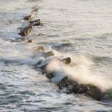 Wave crashing over rocks in ocean at sunrise with long exposure. Wave crashing over rocks in ocean at sunrise Royalty Free Stock Photos