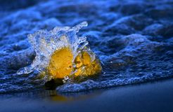 Wave crashing over a stone. A wave crashing over a small stone at the edge of the water Royalty Free Stock Images