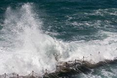 Wave crashing over swimming hole. On day of rough surf stock photos