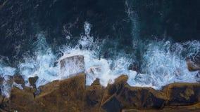 Wave crashing into rocks stock video