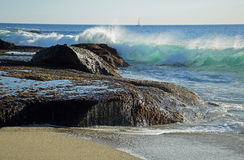 Wave crashing on rocks at Aliso Beach in Laguna Baech, California. Image shows a wave crashing on rocks at Aliso Beach in South Laguna Beach, California. The stock photos