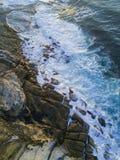 Wave crashing into rocks Stock Image