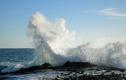 Wave crashing on rocks at West Street Beach in South Laguna Beach,California. Image shows an evening view of a wave crashing on rocks at West Street Beach in stock photography