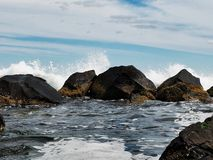 Wave Crashing On Rocks. The white foam of ocean waves crashing on angular boulders sprays into the open air with a small pool of sea water in the foreground Stock Photo