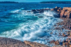 Wave crashing on a rocky shoreline. With ocean in the background Stock Photos