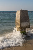 Wave crashing on a stone column. On Caesarea beach, Israel Stock Image