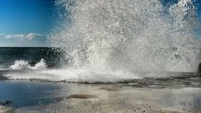 Wave crashing in a sunny day Royalty Free Stock Photography