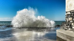 Wave crashing in a sunny day Royalty Free Stock Image