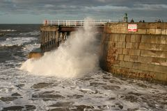 Wave crashing under Whitby pier Royalty Free Stock Photo