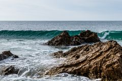 Wave crestring behind rocks near Pacific shore; foam in foreground, sky in background. royalty free stock photo