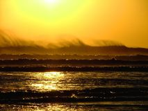 Wave dance. Wind blown wave top at sunset with set of small rollers rolling forward Stock Image