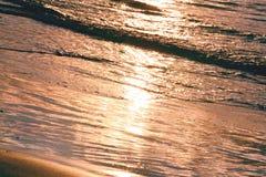 Wave di una spiaggia sabbiosa e di un abbagliamento del sole, fondo rosa, struttura immagini stock