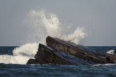 Wave Eats The Rocks. Just a wave crushing on the sea shore Stock Photography
