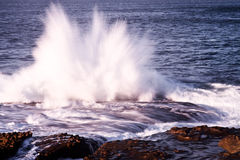 Wave explosion onto rocks. An explosion of water as wave hits rocks Stock Image