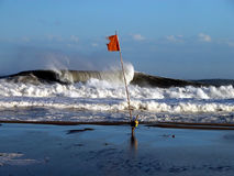 Wave and flag. Ocean beach before the storm Royalty Free Stock Photography