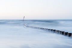 Wave flows around wooden breakwater Stock Photo