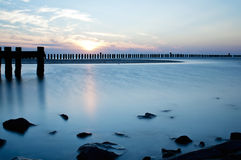Wave flows around wooden breakwater Stock Photography