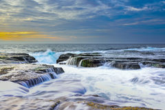 The wave flows over weathered rocks and boulders at North Narrabeen Stock Photography