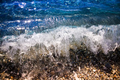 Wave with foam on the beach. Mediteranean coast of Turkey. Toned Royalty Free Stock Photo