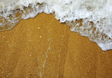 Wave and foam on the sand Stock Photos