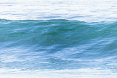 Wave Glassy Water. Ocean wave swell glassy smooth water swell rolling to beach stock image