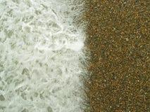 Wave on gravel stones beach. Background Royalty Free Stock Image
