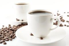 Wave ha fatto dei chicchi di caffè con le tazze di caffè Fotografie Stock Libere da Diritti