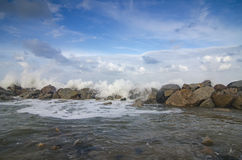 Wave hitting breakwater on the beach over cloudy and blue sky background Royalty Free Stock Image
