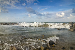Wave hitting breakwater on the beach over cloudy and blue sky background Royalty Free Stock Photography