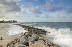 Wave hitting breakwater on the beach over cloudy and blue sky background Royalty Free Stock Photo